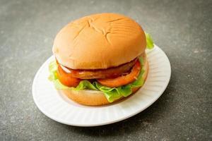 Chicken Burger mit Sauce auf Teller foto