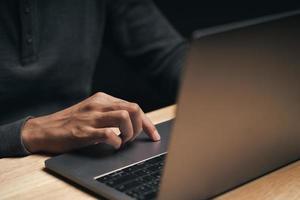 Mann, der einen Laptop auf dem Holztisch benutzt, sucht, surft foto