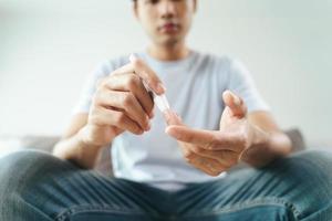 Mann verwendet Lanzette am Finger, um den Blutzuckerspiegel mit dem Glukosemeter zu überprüfen foto