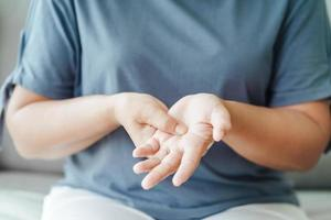 Frau, die auf dem Sofa sitzt, hält ihr Handgelenk foto