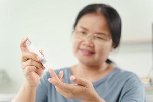 Frau verwendet Lanzette am Finger, um den Blutzuckerspiegel mit dem Glukosemeter zu überprüfen foto