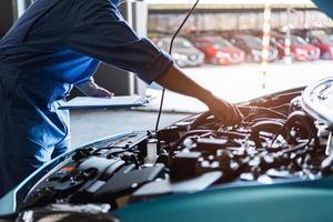 Automechaniker hält Zwischenablage und überprüft das Wartungsfahrzeug foto