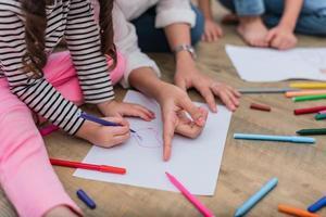 geschlossene Hände der Mutter, die kleinen Kindern das Zeichnen von Cartoons beibringt foto