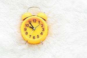 gelber Wecker auf weißer Wolle. spätes und faules Zeitkonzept foto