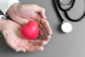 Arzthände halten und geben dem Patienten ein rotes Massageherz, um sich zu erholen foto