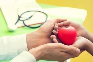 Doktorhände, die geduldigen kleinen Kindern rotes Massageherz geben foto