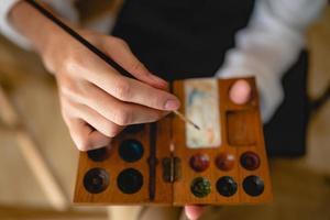 Kreativer Künstler, der an Farben arbeitet, um Bilder mit Pinsel zu zeichnen foto
