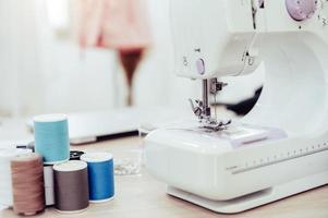 Nahaufnahme der Nähmaschine mit Modedesigner foto