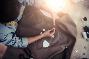 Blick von oben auf die schöne Schneiderin, die Kleiderstoff näht foto