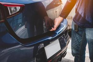 Mannhand öffnet Heckklappe Kofferraum durch Berühren des Sensors foto