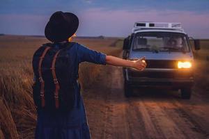 Frau Tourist in Hut mit Rucksack stoppt Auto auf der Straße foto