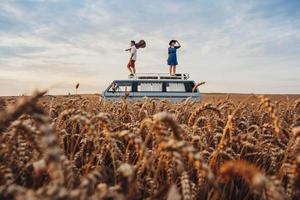 Mann mit Gitarre und Frau stehen auf dem Dach eines Autos in einem Weizenfeld foto