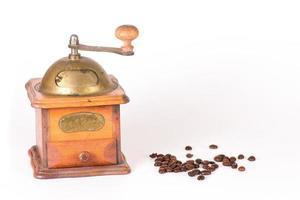 Kaffeemühle mit einigen Körnern auf einem weißen verstreut foto
