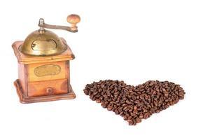 Kaffeemühle mit Kaffeebohnen in Herzform foto