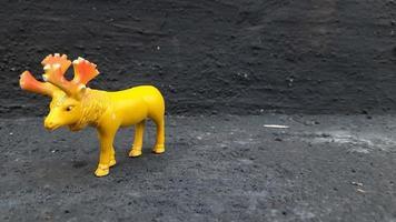 Nahaufnahme einer gelben Hirschtierspielzeugpräsentation in grauem Hintergrund foto
