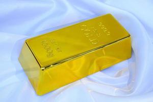 Goldbarren 1 kg auf glattem, elegantem weißem Seidenstoff-Luxus-Stoff-Hintergrund foto