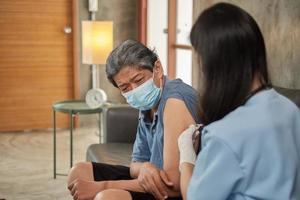 Eine asiatische Ärztin impft zu Hause einen älteren Mann. foto