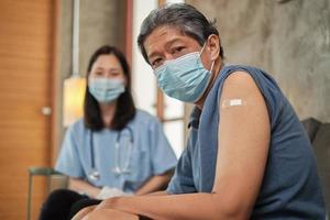 älterer männlicher Patient mit Pflaster am Arm geimpft. foto