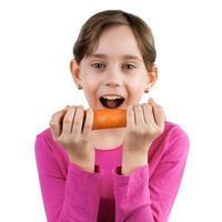 glückliches Mädchen, das eine große Karotte isst foto