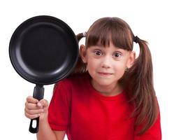 kleines Mädchen, das eine Bratpfanne hält foto