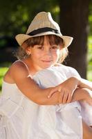 fröhliches braunäugiges Mädchen in einem stilvollen Hut foto