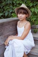 süßes Mädchen mit Hut sitzt auf der Veranda foto