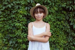 entzückendes Mädchen, das auf einem Hintergrund von Laub steht foto