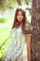 Mädchen in einem Sommerkleid, das an einen alten Baum gelehnt ist foto