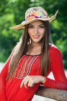 Mädchen in einem roten Kleid und Hut foto