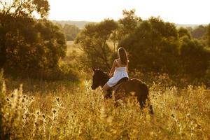 junge Frau auf einem braunen Pferd foto