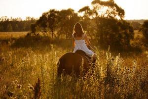 Frau in einem Kleid reitet auf einem erwachsenen Pferd foto
