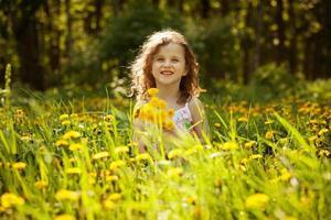 kleines Mädchen mit einem Strauß Löwenzahn foto