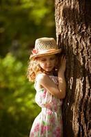 kleines Mädchen mit Strohhut, das in der Nähe eines Baumes steht foto