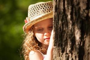 Mädchen mit Hut, das in Gedanken neben dem Baum steht foto