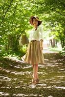 schöne elegante Frau mit Hut unter grünem Laub foto