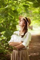 schöne Frau mit Hut zwischen grünem Laub foto