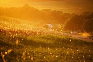 Auto auf einer Landstraße zwischen Feldern unterwegs foto