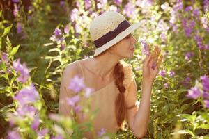 schöne Frau, die den Duft von Wildblumen genießt foto