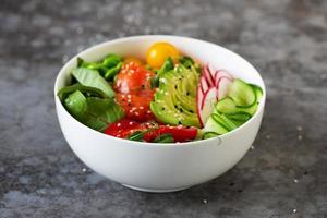 Teller mit Avocado, Lachs, Tomate und Quinoa-Poke foto