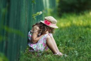trauriges kleines Mädchen, das auf Gras sitzt foto