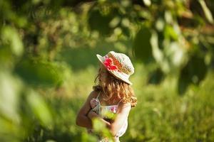 Mädchen mit Hut steht im Laub foto