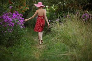 Frau mit Hut geht zwischen den Blumen foto