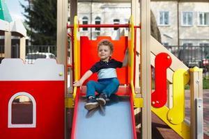 Junge macht eine Fahrt auf einem Kinderhügel foto