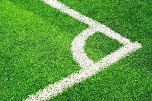 grünes Fußballfeldgras und weiße Ecklinie foto