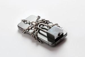 Smartphone mit Kette auf weißem Hintergrund gesperrt foto