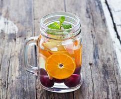 Tasse leckeres Erfrischungsgetränk aus Mixfrüchten mit Minze foto