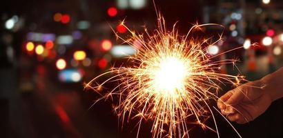 Mannhand, die Wunderkerze oder Feuerwerk auf Straßennachthintergrund hält foto