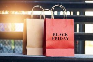 schwarzer freitag wort auf roten und braunen papiereinkaufstüten foto