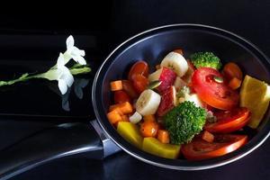 sauberes Essen, Obst und Kräuter in der Pfanne auf dunklem Hintergrund mischen foto