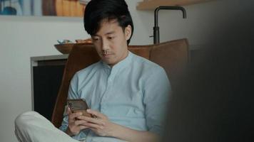 Mann im Stuhl schaut zu und benutzt Handy foto